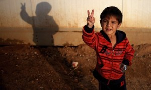 Syrian boy Rayyan Nasser makes a peace sign at Zaatari refugee camp in Mafraq, Jordan